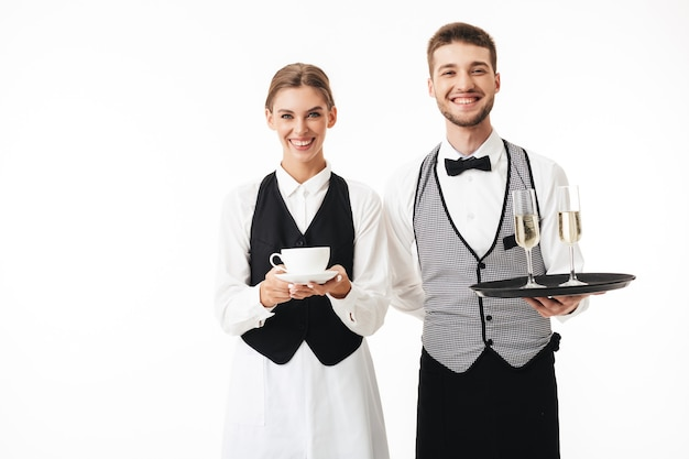 Young cheerful waiter holding tray with glasses of champagne and pretty waitress with cup of coffee in hands happily