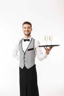 Young cheerful waiter in uniform happily