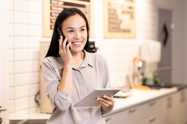 Young cheerful waitress or manager of restaurant communicating with client on mobile phone while using digital tablet by workplace