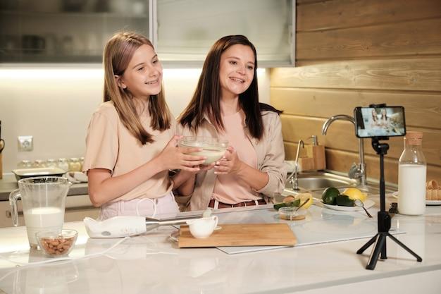 若い陽気な女性と彼女のかわいい10代の娘は、スマートフォンのカメラを見ながらアイスクリームの材料を混ぜたガラスのボウルを示しています