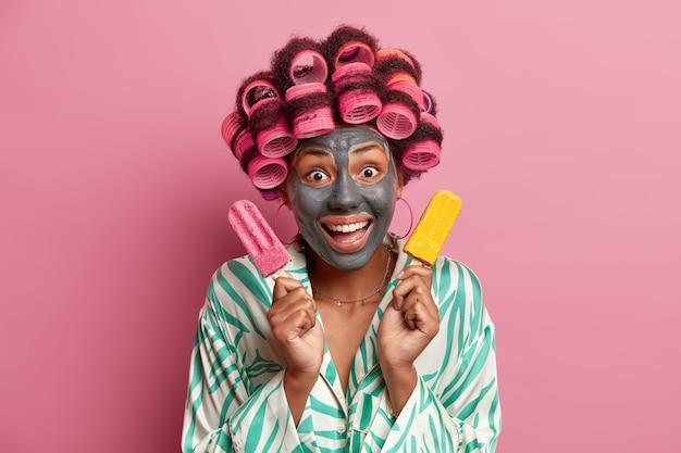 La giovane donna allegra applica una maschera all'argilla per una pelle sana e riduce le linee sottili, posa con un delizioso gelato freddo, esegue procedure di peeling di bellezza per il viso, indossa bigodini, indossa una vestaglia