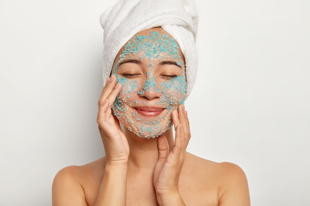 Young cheerful woman applies natural scrub on face, touches cheeks, keeps eyes closed, wears towel, has beauty procedures after taking shower, models indoor. female model with blue sea salt on skin