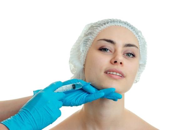 Молодая веселая женщина у пластического хирурга изолирована на белой стене