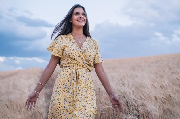 Молодая веселая женщина, наслаждаясь природой во время прогулки по пшеничному полю.