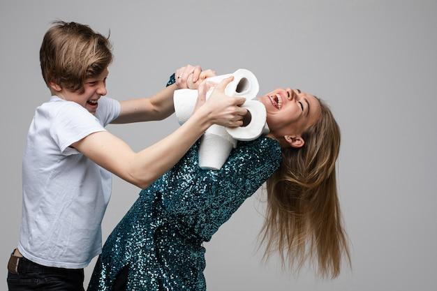 Молодая веселая женщина борется за много туалетной бумаги с молодым мальчиком, портрет на белом фоне