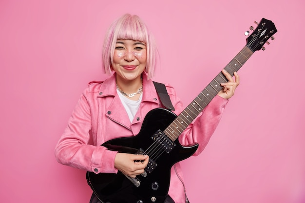 Young cheerful woman guiratist with pink bobbed hairstyle plays favorite music on acoustic electric guitar ejoys hobby and leisure activities poses indoor wears jacket. talented musician or soloist
