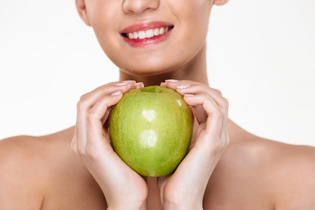 Young cheerful woman holding big green apple in both hands like heart shape