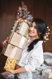 Young cheerful woman holding christmas presents