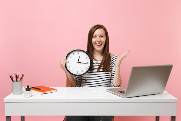 Молодая веселая женщина, держащая круглый будильник, разводя руками, сидит за белым столом с современным ноутбуком, изолированным на пастельно-розовом фоне. достижение бизнес-концепции карьеры. скопируйте пространство.