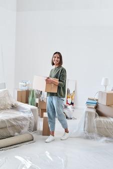 Молодая веселая женщина в повседневной одежде несет коробку с вещами во время движения по гостиной новой квартиры или дома