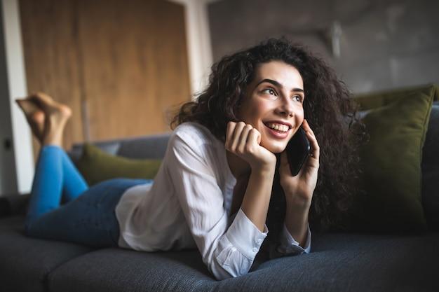 携帯電話で話しているソファの若い陽気な女性