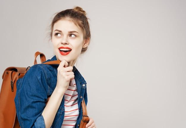 ファッションの服のバックパックの学生のライフスタイルの若い陽気な女性