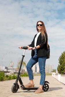 흐린 하늘과 도시 환경의 배경에 카메라 앞에서 전기 스쿠터에 서있는 스마트 캐주얼에 쾌활한 젊은 여자