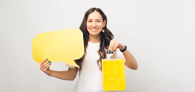Молодая веселая женщина держит желтую хозяйственную сумку и речевой пузырь.