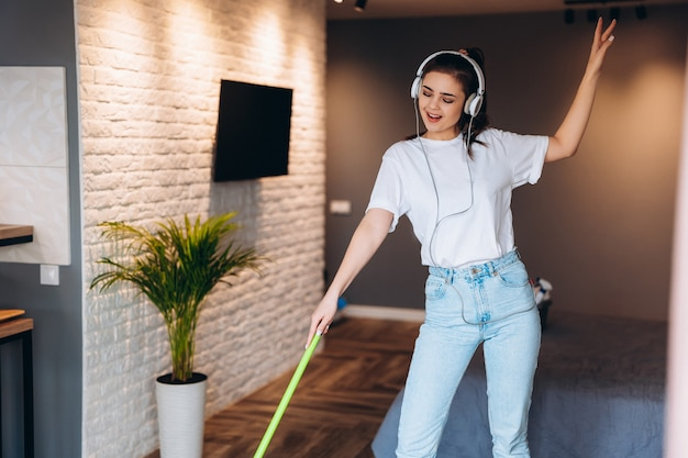 Young cheerful woman is washing floor in room with mop having fun