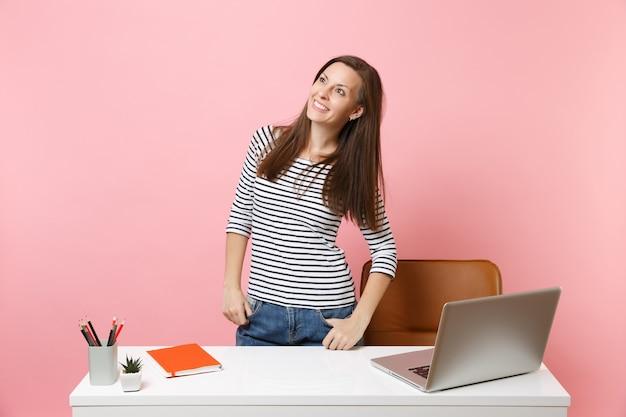 パステルピンクの背景に分離された現代的なpcラップトップで仕事を脇に見て白い机の近くに立っている若い陽気な女性。業績ビジネスキャリアコンセプト。広告用のスペースをコピーします。