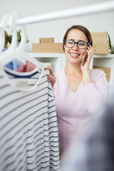 Young cheerful woman looking through new casualwear seasonal collection