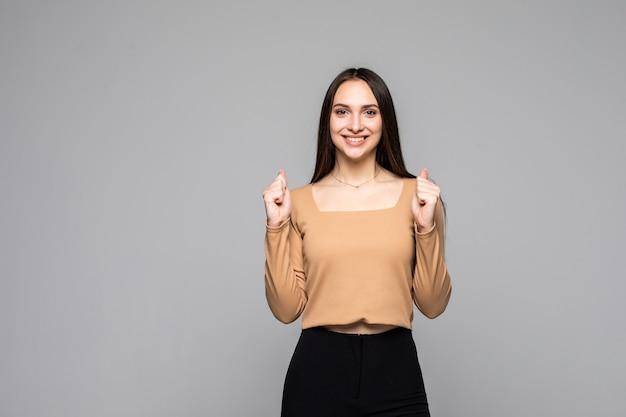 Молодая веселая женщина делает жест победителя и улыбается изолированно над серой стеной