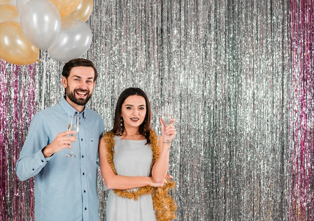 Young cheerful woman near handsome man with glasses near tinsel and balloons