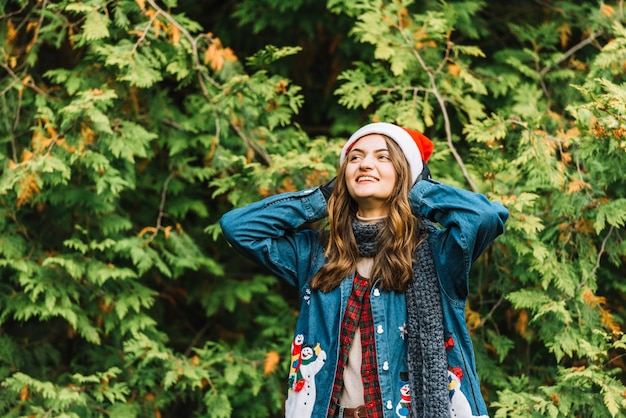 Young cheerful woman in party hat near coniferous branches
