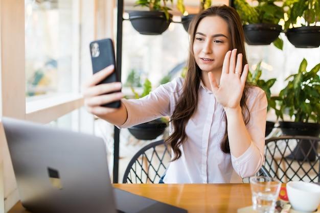 友達とチャットするためにスマートフォンで自分自身を撮影しながらポーズをとる若い陽気な女性、カフェに座っている間携帯電話で自画像を作る魅力的な笑顔の流行に敏感な女の子