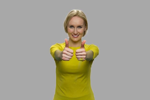 両手で親指を立てて若い陽気な女性。灰色の背景に対してカメラを見て幸せな女性。