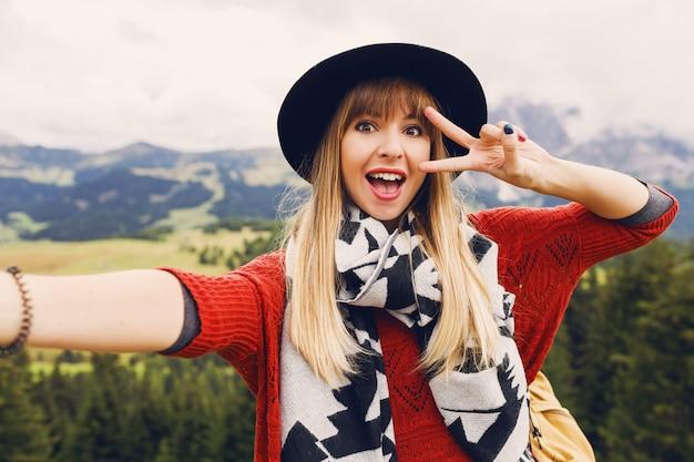 Giovane donna allegra sorridente, prendendo selfie e mostrando le mani di segni