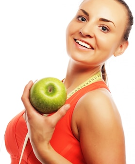 Young cheerful woman in sports wear with apple, isolated over white