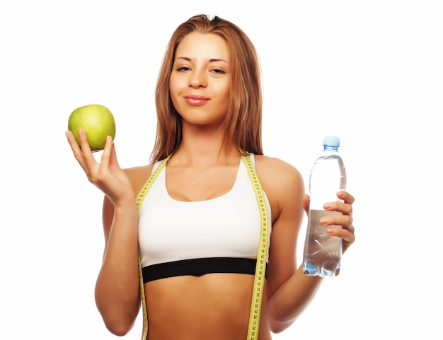 Young cheerful woman in sports wear with apple and water, isolated over white