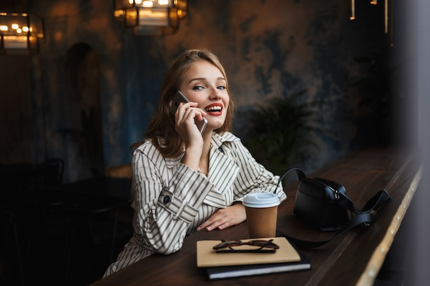 Young cheerful woman in striped trench coat talking on cellphone happily