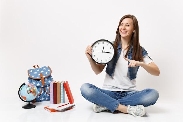 Giovane studentessa allegra in abiti di jeans che punta il dito indice sulla sveglia seduta vicino al globo, zaino, libri scolastici isolati