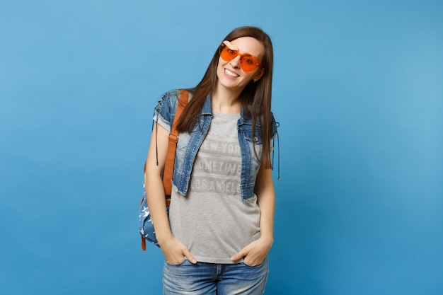 青い背景で隔離のポケットに手を入れてオレンジ色のハートのメガネを身に着けているバックパックとデニムの服を着た若い陽気な女性の学生。大学での教育。広告用のスペースをコピーします。