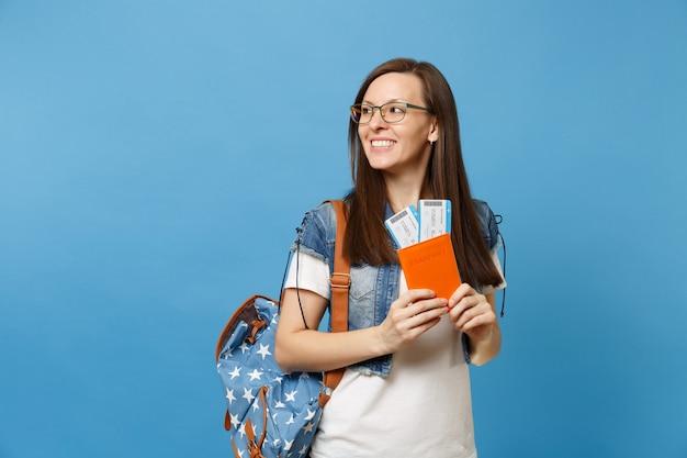 Молодой жизнерадостный студент-женщина в очках с рюкзаком, глядя в сторону, держите паспорт, билеты на посадочный талон, изолированные на синем фоне. обучение в вузе за рубежом. концепция полета авиаперелета.