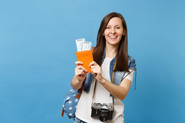 Молодой жизнерадостный студент-женщина с рюкзаком и ретро-фотоаппаратом на шее, держа билеты на посадочный талон паспорта, изолированные на синем фоне. обучение в вузе за рубежом. авиаперелет.