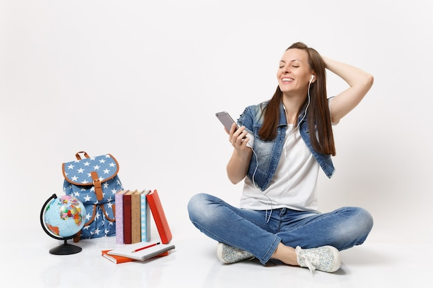 Young cheerful woman student with earphones keeping hand on head listen music holding mobile phone near globe backpack books isolated