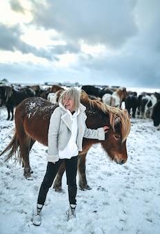 若い陽気な女性の観光客は、雪をかぶった山の斜面にある野生の馬の牧草地の中で楽しんでいます。