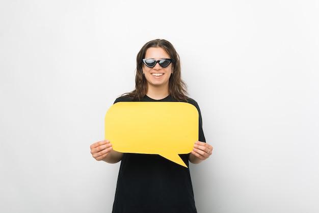 Молодая веселая женщина в солнечных очках держит желтый речевой пузырь.