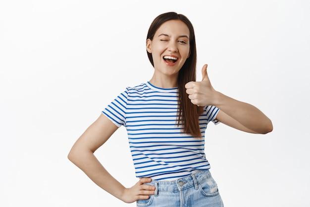 Молодая жизнерадостная женщина подмигивает и показывает палец вверх, довольная улыбка, довольная чем-то хорошим, хвалит хорошую работу, комплименты, стоит в футболке у белой стены