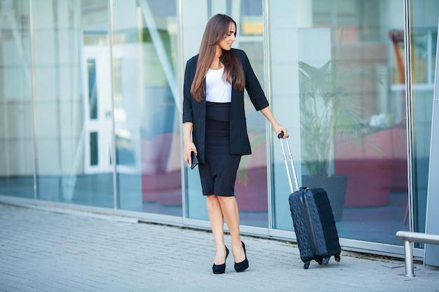 スーツケースを持つ若い陽気な女性。旅行、仕事、ライフスタイルの概念