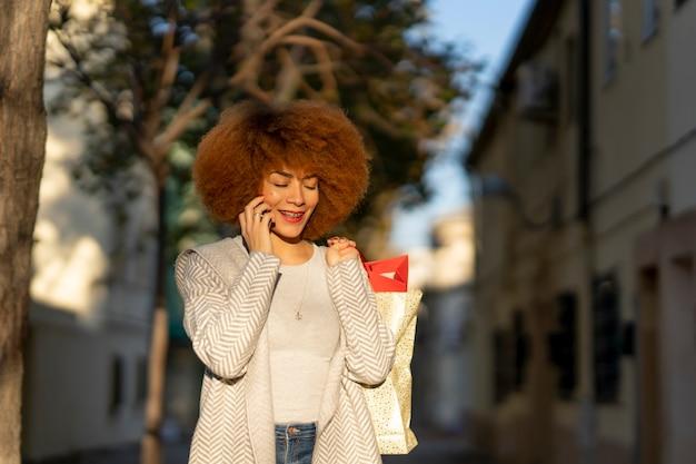 ショッピングバッグを持って街の通りでスマートフォンで話しているアフロ髪の若い陽気な女性
