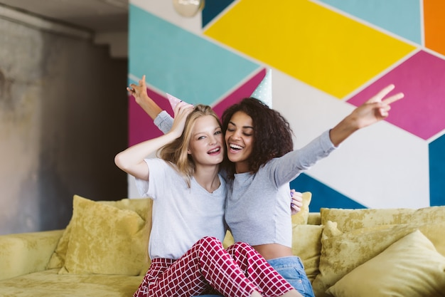 Young cheerful woman with blond hair in birthday cap and pretty african american woman with dark curly hair happily spending time together with colorful wall  at home