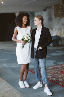 Young cheerful woman with blond hair in black jacket and smiling african american woman with dark curly hair in white dress with flowers in hand happily looking at each other on wedding ceremony