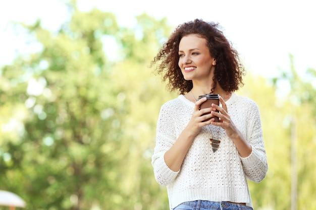 公園を歩いてコーヒーを飲む若い陽気な女性