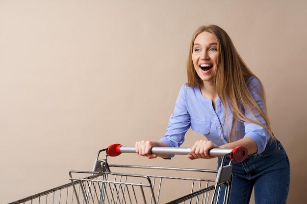 Молодая веселая женщина с пустой тележкой на бежевом фоне