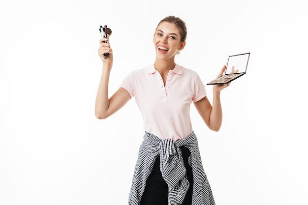 メイクブラシとパレットを手に楽しく元気な若い女性