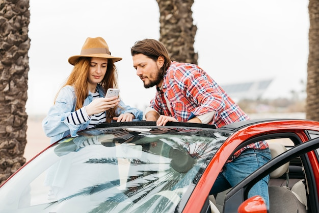 Young cheerful woman with smartphone near man leaning out from car