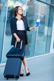 Young cheerful woman with a suitcase, the concept of travel, work, lifestyle
