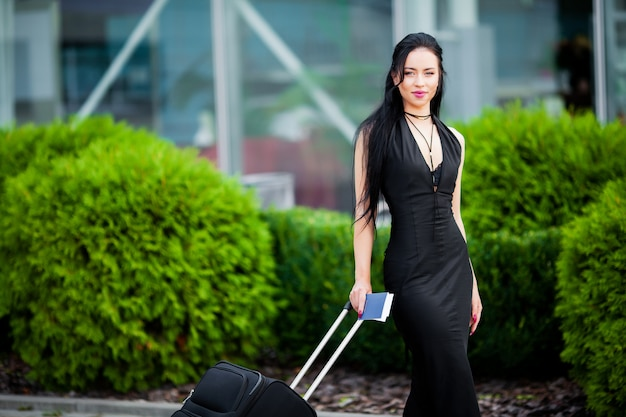 Young cheerful woman with a suitcase. the  of travel and work