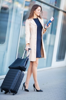 Young cheerful woman with a suitcase.