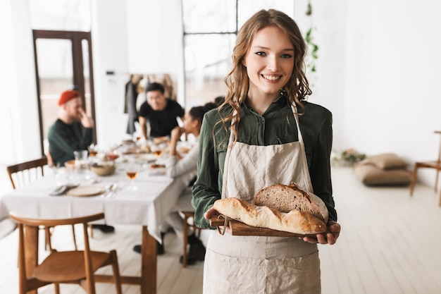Young cheerful woman with wavy hair in white apron holding bread on board in hands, happily